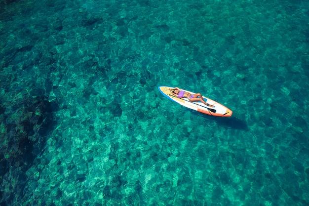 サーフボードでビキニで横たわっている間ポーズ美しいボディとセクシーな笑みを浮かべて少女