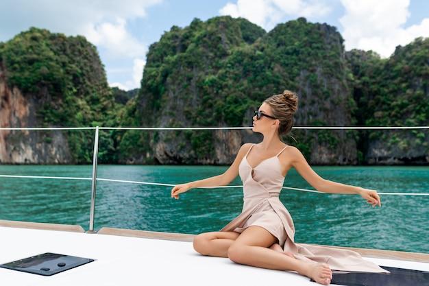 ヨットの端に立っているベージュのドレスで愛らしい若い女性の屋外撮影