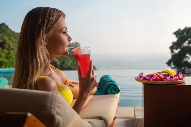 魅力的なブロンドは、インフィニティプールの近くのサンベッドでリラックスし、スイカのスムージーを飲みます