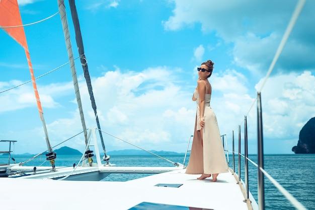 Открытый выстрел очаровательны молодой женщины в бежевом платье, стоя на краю яхты