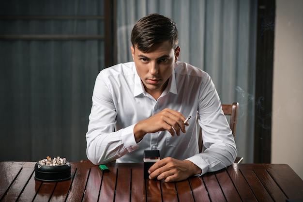 Плохие привычки. портрет парня, сидящего за столом, на котором стоит пепельница, полная сигарет