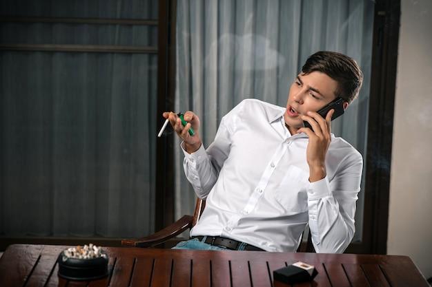 Плохие привычки. портрет парня позирует сидя за столом разговаривает по телефону