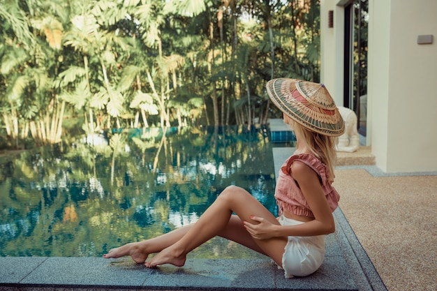 壊れやすいブロンドの女の子がプールの近くのアジアの帽子に座っています。暑い国で休む