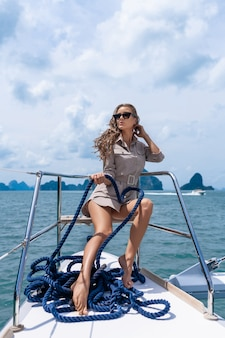 Привлекательная и шикарная брюнетка сидит и катается на современной яхте.