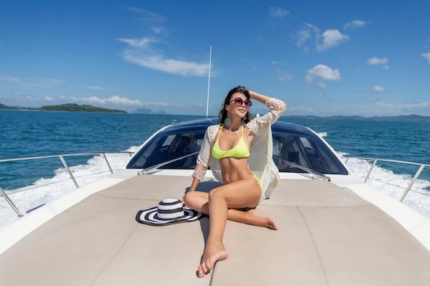 豪華ヨットの端に座ってセーリング旅行中に海を探している愛らしい若い女性のファッション写真