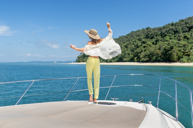 背面図:ヨットの端に夏のスーツで愛らしい若い女性の屋外撮影