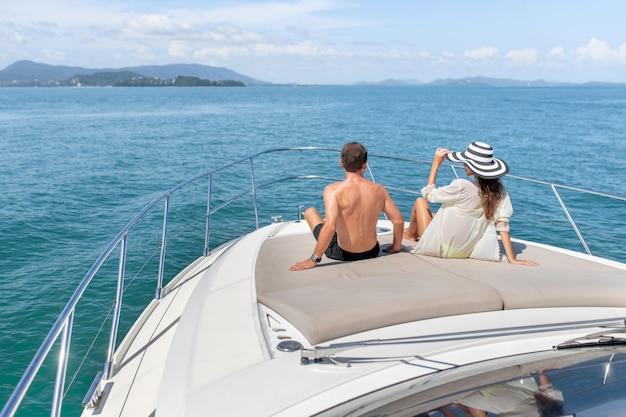 背面図:男と女は豪華な白いヨットで日光浴します。