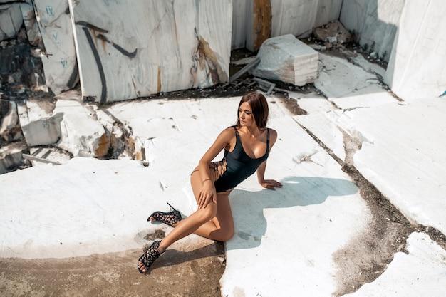 白い岩でポーズをとって黒い水着に身を包んだ魅力的なホット若いブルネット