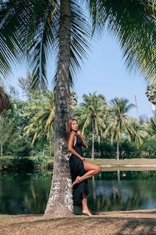 大きな湖でヤシの木の近くに立っているイブニングブラックドレスでハンサムなアジアモデル