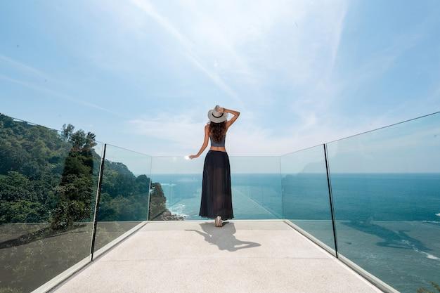 Стройная девушка в шляпе и длинной юбке стоит на прозрачном балконе и смотрит вдаль на красивый морской пейзаж