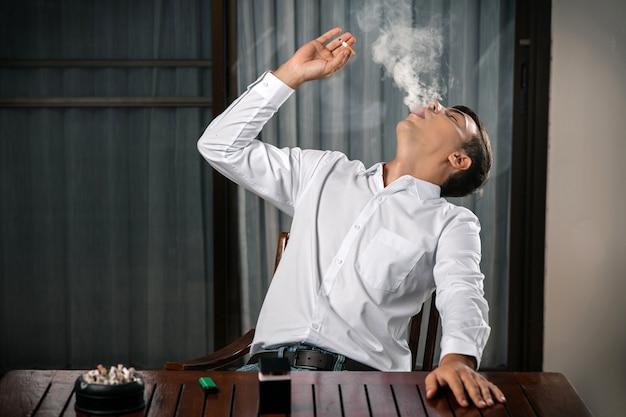 Плохие привычки. портрет парня, сидящего за столом, на котором стоит пепельница, полная сигарет, зажигалка с сигаретой в руке, выдувающий дым, который был отброшен назад. никотин.
