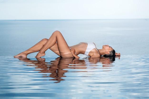 太陽を楽しんでいるプールの端にある水の上に横たわっている白いビキニのゴージャスな女性。夏の日にスイミングプールでリラックスした女性。テキスト用のスペース