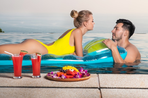 美しいカップルがプールで泳いでいます。トロピカルフルーツと新鮮なスイカ。熱帯の休暇
