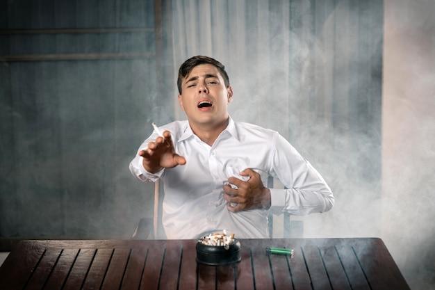 Портрет молодого парня позирует, сидя за столом, на котором стоит полная пепельница, держит зажженную сигару в руке, держит его сердце. смерть от сигарет. боль в груди. стоп.