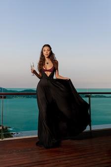 Роскошная брюнетка позирует в черном длинном платье в дорогих украшениях с бокалом вина на балконе. роскошный вид на тропический остров и море