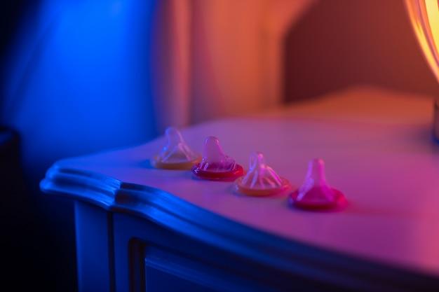 Куча презервативов открыта, лежат на прикроватном деревянном столе возле лампы. презервативы. защищенная любовь. крупный план. защита от вич-инфекции. страсть.