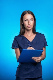 青いフォルダーと彼女の手にペンで、青い背景に立っているポーズ青い手術スーツで彼女の髪の美しいブルネット。青いフォルダーにペンで書き込みます。