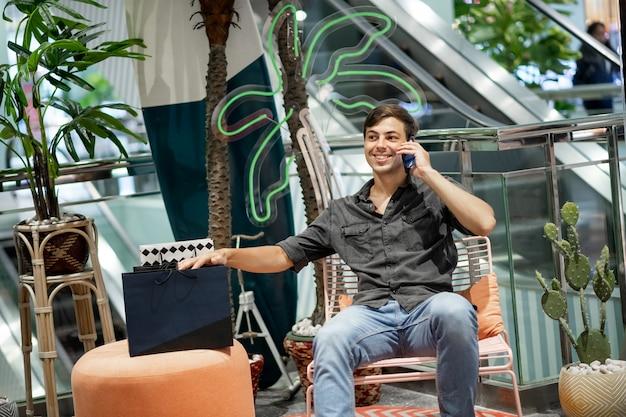 笑顔の若い男がショッピングセンターのラウンジエリアの椅子に座って電話で話し、幸せな感情を表現し、オットマンにある買い物袋で手をつないでいます。
