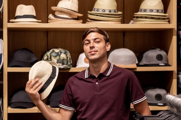Молодой человек в бордовой футболке и бежевых брюках с соломенной шляпой в руке позирует среди деревянных полок с различными вещами с сумками разных цветов в руках. портрет. скидки. распродажа.