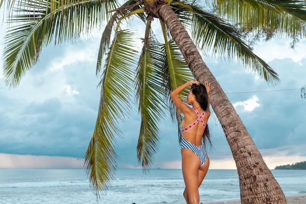 日光浴の後、エキゾチックなリゾートでポーズをとって光沢のある肌を持つ格好の良いアジアの女の子。ヤシの木の近くに立っているトレンディなビキニで官能的なブルネットの女性。夏休み