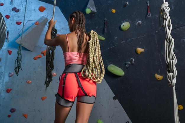 Вид сзади: молодая женщина в альпинистское снаряжение, позирует с веревкой для страхования. концепция скалолазания
