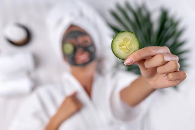 あいまいな背景に彼女の顔にマスクをしたドレッシングガウンのポーズモデルの手で前景にキュウリのスライスの写真。自然化粧品のコンセプト。