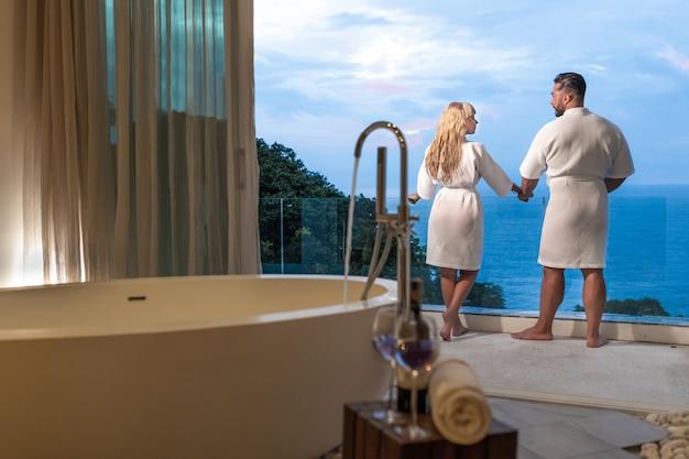 Вид сзади: красивая пара в халатах, любуясь панорамным видом на море в своей ванной комнате. медовый месяц. семейный отдых