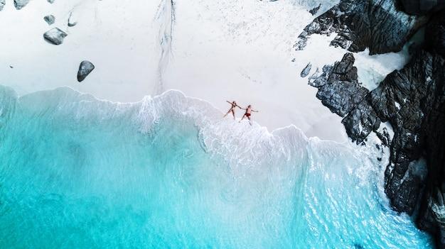 Пляжный дрон вид на тропический остров, белый пляж с волнами, пара ложится на пляж