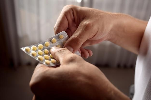 黄色い錠剤を取り出して男性の手