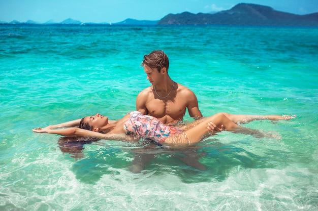 ハンサムな男と彼のガールフレンドは、ターコイズブルーの海で泳いでいます。熱帯の島の楽園の休日。