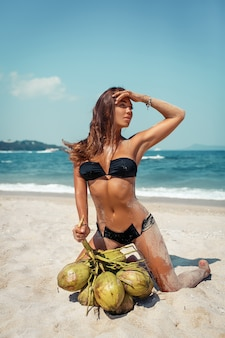 熱帯のビーチで彼女の手にココナッツの束と座っているトレンディな水着の美しい日焼けした少女。