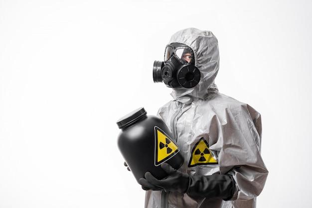 プロフィール写真:放射線防護服と防毒マスクをかぶった男が、手に放射能標識のある大きな黒い瓶を抱えています。生物学的危険。