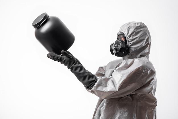 プロフィール写真:放射線防護服と防毒マスクを着た男性が手に大きな黒い瓶を抱えています。生物学的危険。