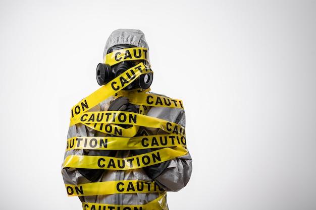 白い背景のスタジオ写真:放射線防護服を着た男が黄色のテープ「注意」に包まれています。