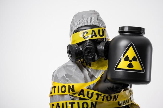 放射能汚染。黄色のテープ「注意」に包まれた保護服を着た科学者が、放射線の危険の兆候のある黒い容器を手に持っています。コピースペース