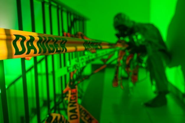 防護服と防毒マスクをかぶったぼやけた男が禁断のテープを引き裂きます。自己分離の違反。生物学的危険。緑色の光