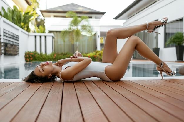 プールの近くで日光浴をする白いワンピース水着のセクシーなモデル。豪華なヴィラでリラックス