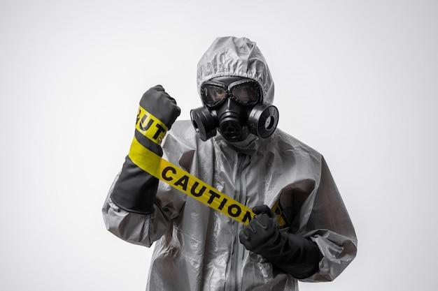 防護服と防毒マスクを着た男は、孤立した白地に黄色のテープ「注意」を手に持っています。検疫。生物学的および化学的危険。