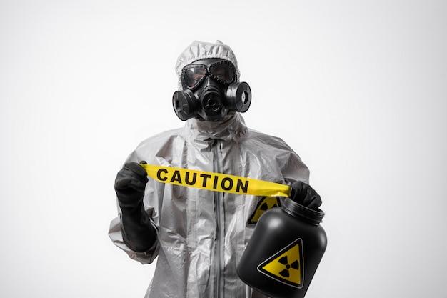 防護服と防毒マスクの男は、孤立した白地に黄色のテープ「注意」を保持しています。検疫。生物学的および化学的危険。