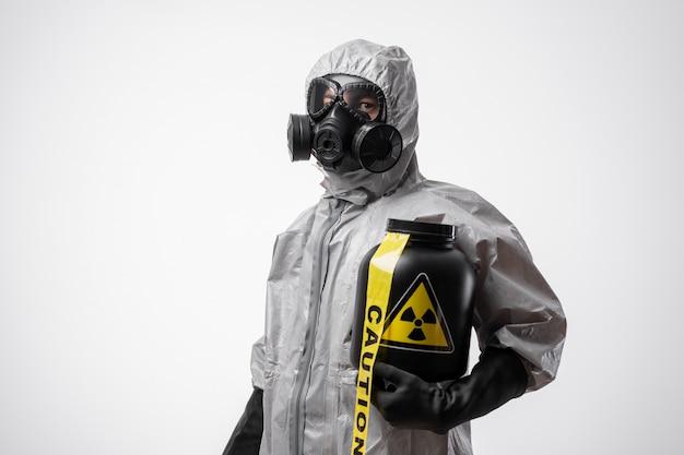 防護服と防毒マスクを着た男性が、放射性廃棄物の黒い瓶と黄色の注意テープを持っています。