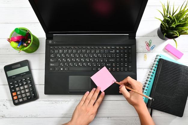Женские руки, пишущие карандашом на розовой записке