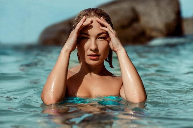 海の水で官能的な美しい若い女性の肖像画をクローズアップ。モデルはカメラを見つめます。ファッション