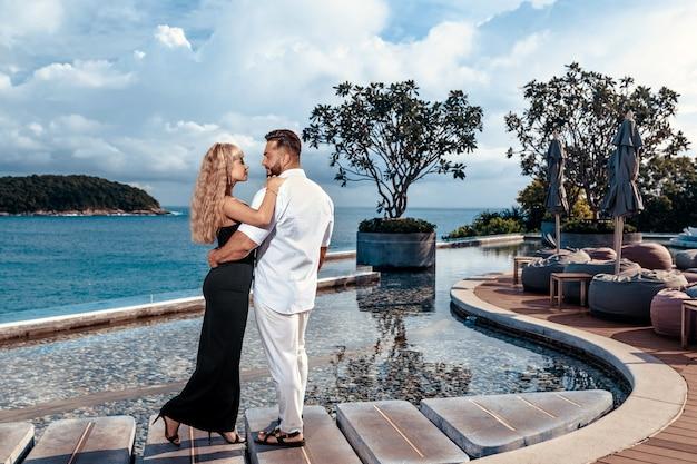 Пара в элегантной одежде стоит возле пейзажного бассейна