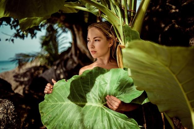 美容顔。自然化粧と緑の葉の植物で健康的な肌を持つ女性モデル。美しい白人女性の熱帯のビーチの肖像画。自然と美しさ。