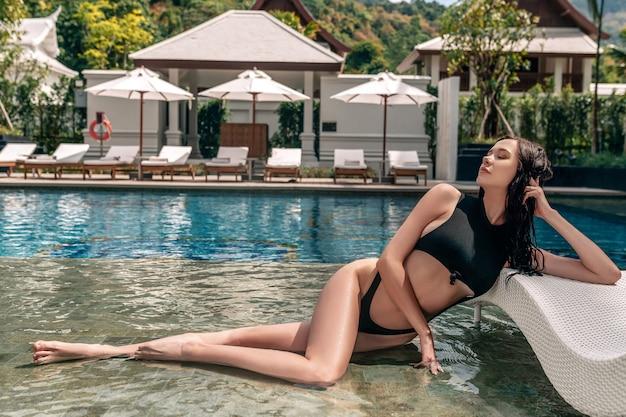 黒のビキニを着てプールでポーズをとる女性