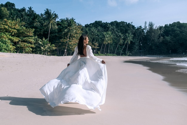 花嫁のウェディングドレスでビーチを歩いて