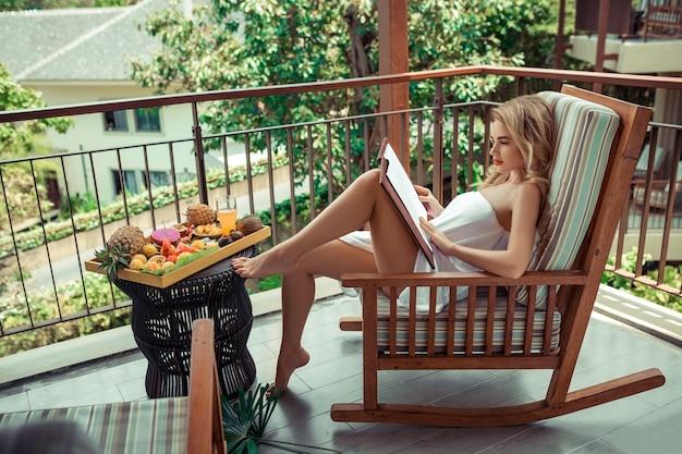 緑の上の屋外レストランに座っていると笑顔の彼女の手でメニューを持つ若い女性。トロピカルフルーツとジュースのテーブル