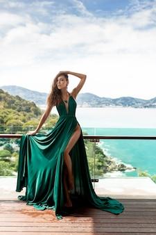 バルコニーをポーズ長い緑のドレスでほっそりした脚を持つ非常に美しい女性。自然の風景-青い海と大きな緑の山々
