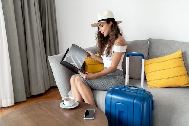 Молодая женщина прибыла на курорт. красивая девушка в классической одежде и шляпе сидит на диване в гостинице с чемоданом путешествует и выбирает экскурсии и аттракционы в журнале