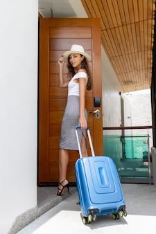 Молодая услаженная женщина с голубым чемоданом и в двери отверстия шляпы на современном гостиничном номере. путешествия и отдых